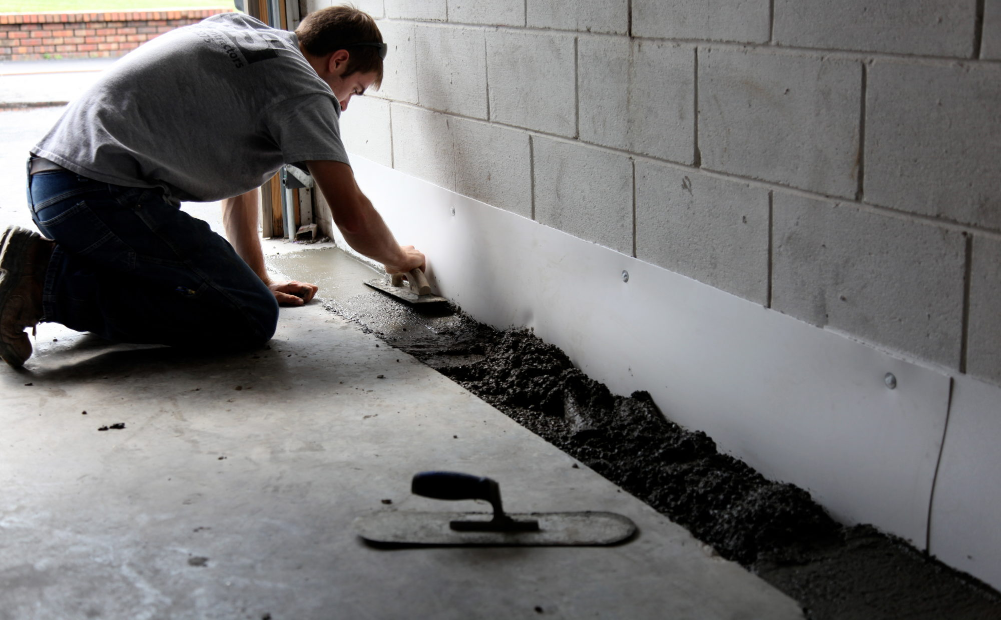 United Structural Systems, Inc. is shown waterproofing the interior of a home by covering drain pipes that are connected to a sump pump.